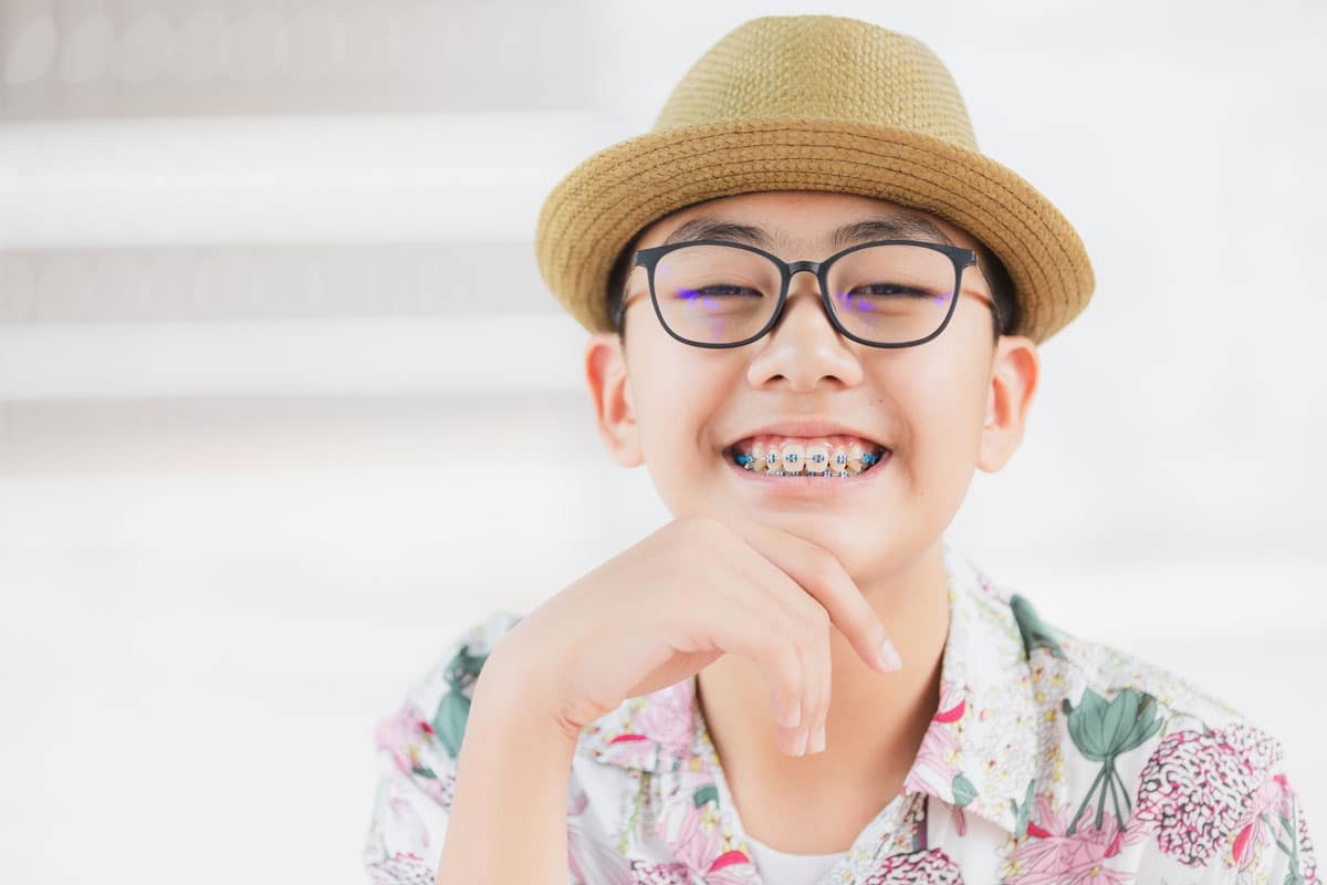 smiling teen boy with braces, black framed glasses and small straw hat