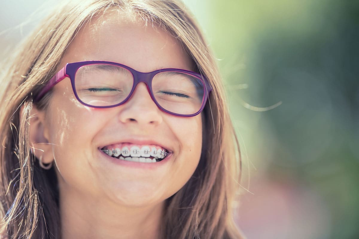 young girl with purple glasses and braces, smiling