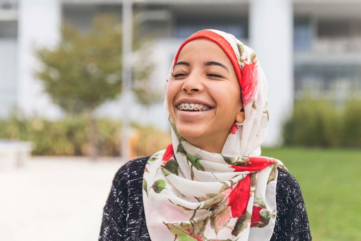 young girl with head scarf and braces, smiling